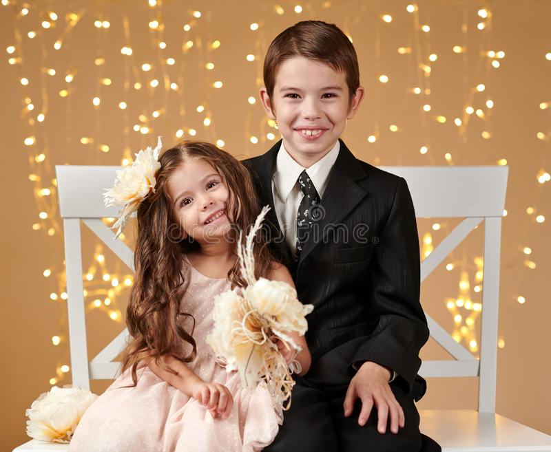 Deux enfants garçon et fille sont dans des lumières de Noël, fond jaune, concept de vacances d'hiver photo libre de droits