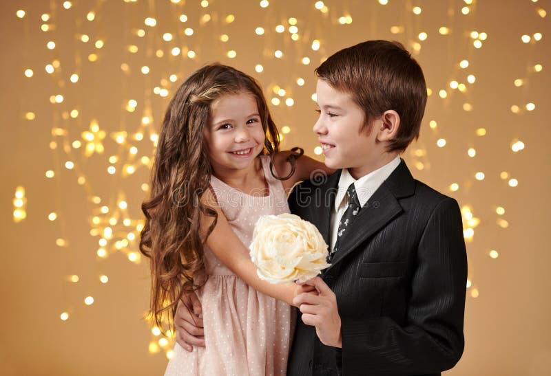 Deux enfants garçon et fille sont dans des lumières de Noël, fond jaune, concept de vacances d'hiver photos stock