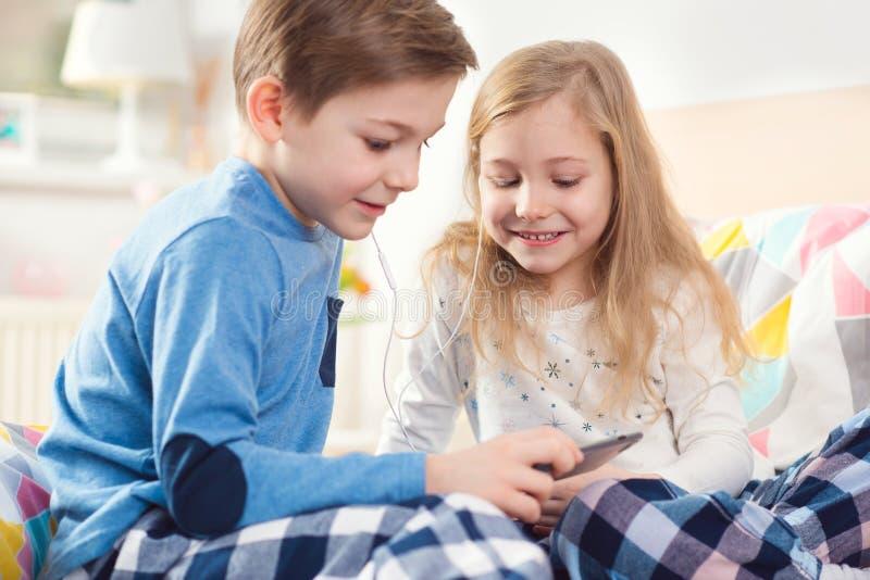 Deux enfants heureux d'enfants de mêmes parents ayant l'amusement et la musique de écoute avec images libres de droits