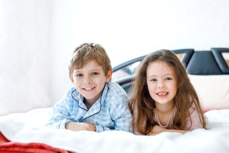 Deux enfants heureux dans des pyjamas célébrant la partie de pyjama École maternelle et écolier et fille ayant l'amusement ensemb image stock