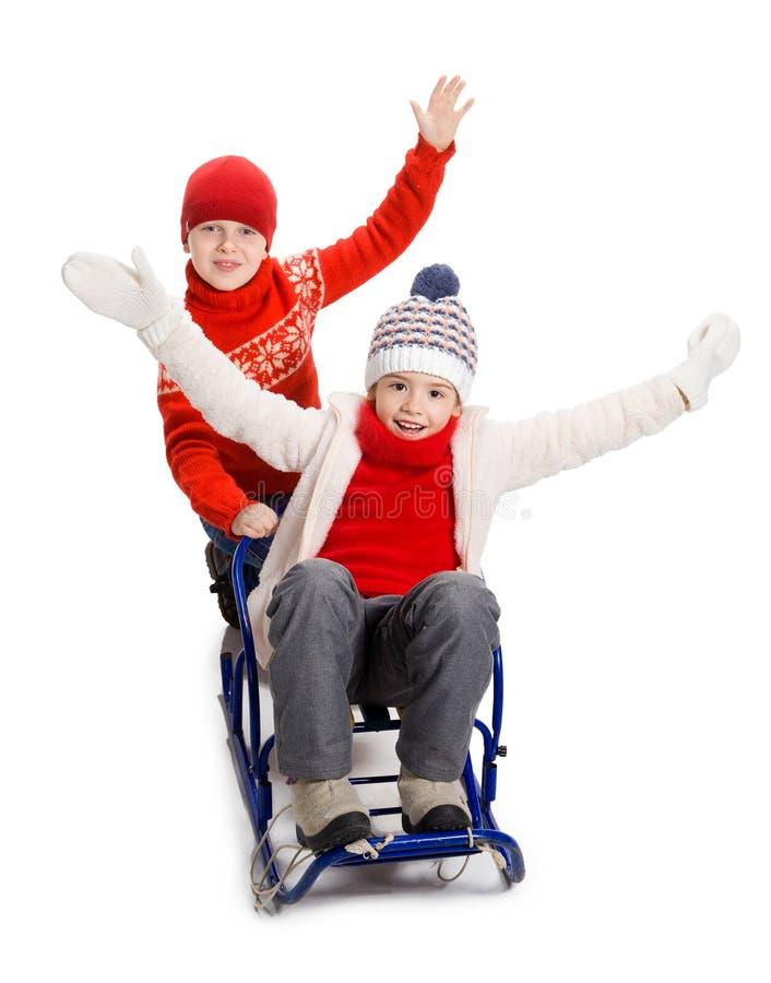 Deux enfants heureux dans des vêtements d'hiver sur le traîneau image stock