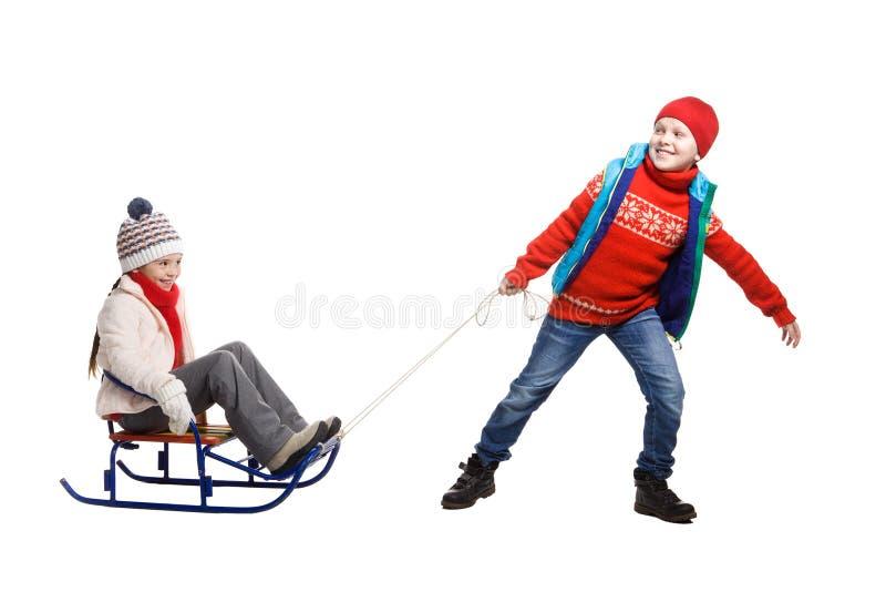 Deux enfants heureux dans des vêtements d'hiver sur le traîneau photo stock