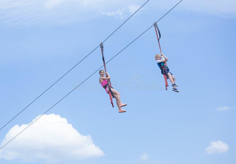 Deux enfants heureux jouant sur une ligne vue de fermeture éclair de dessous images libres de droits