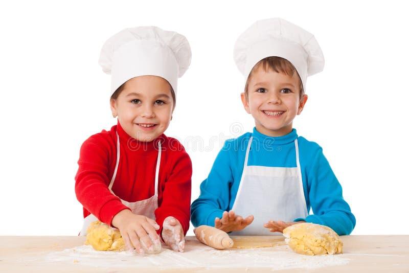 Deux enfants malaxant la pâte ensemble photo stock