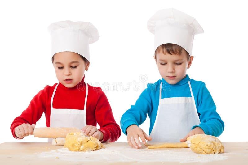 Deux enfants malaxant la pâte ensemble image libre de droits