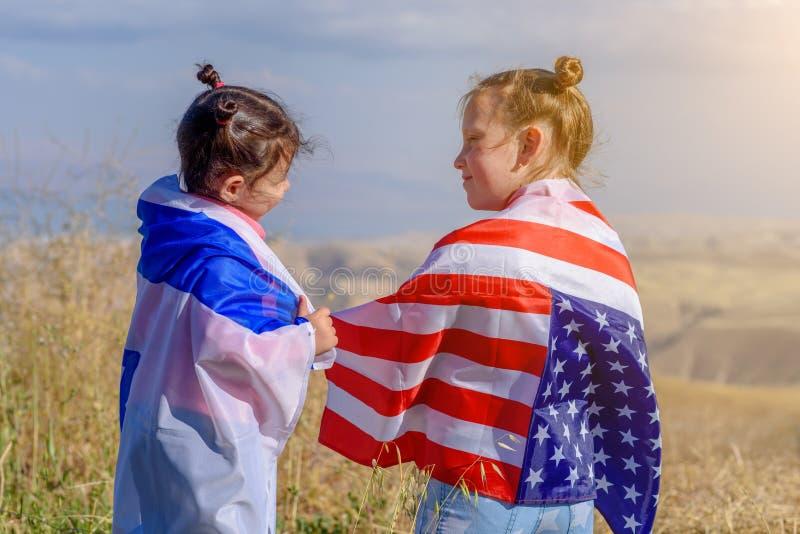 Deux enfants mignons avec des drapeaux d'Américain et de l'Israël photographie stock libre de droits