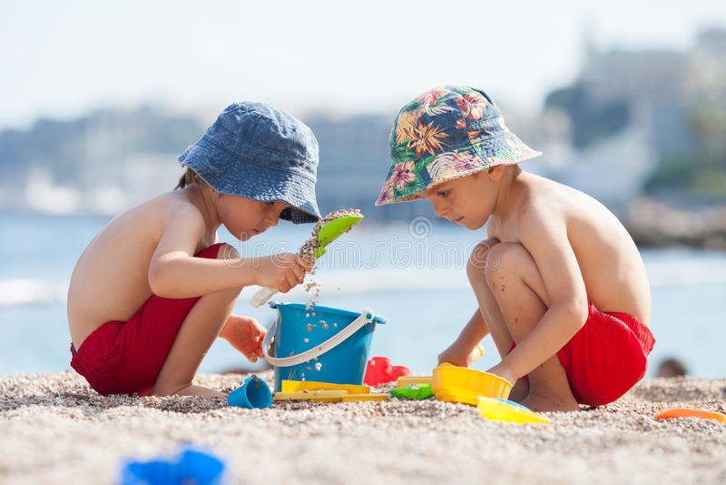 Deux enfants mignons, jouant dans le sable sur la plage photo libre de droits