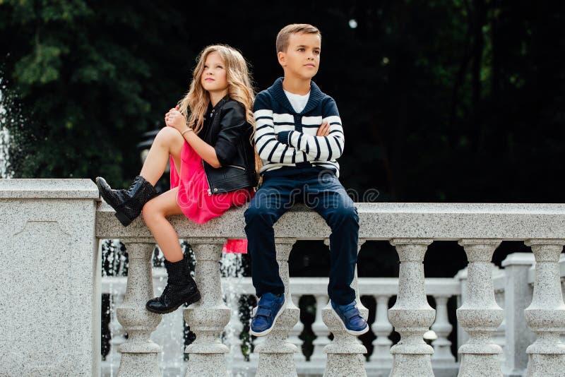 Deux enfants mignons s'asseyent sur la balustrade fontaine de Marbre-pierre image libre de droits