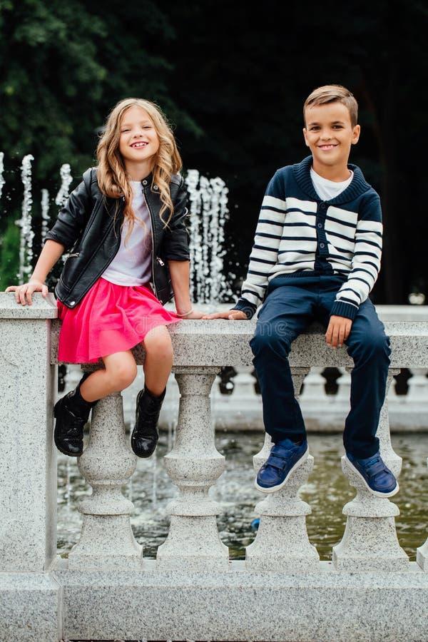 Deux enfants mignons s'asseyent sur la balustrade fontaine de Marbre-pierre photographie stock