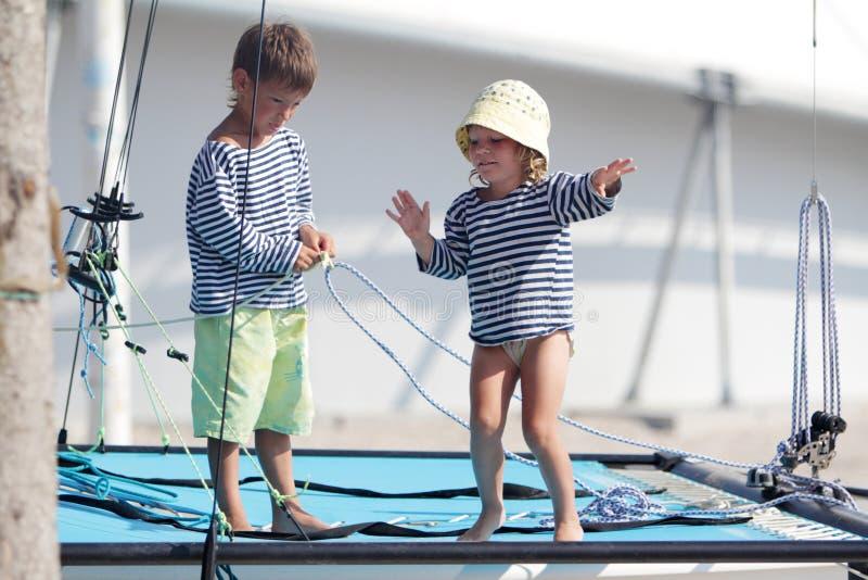 Deux enfants mignons sur le catamaran/yacht de mer photos stock
