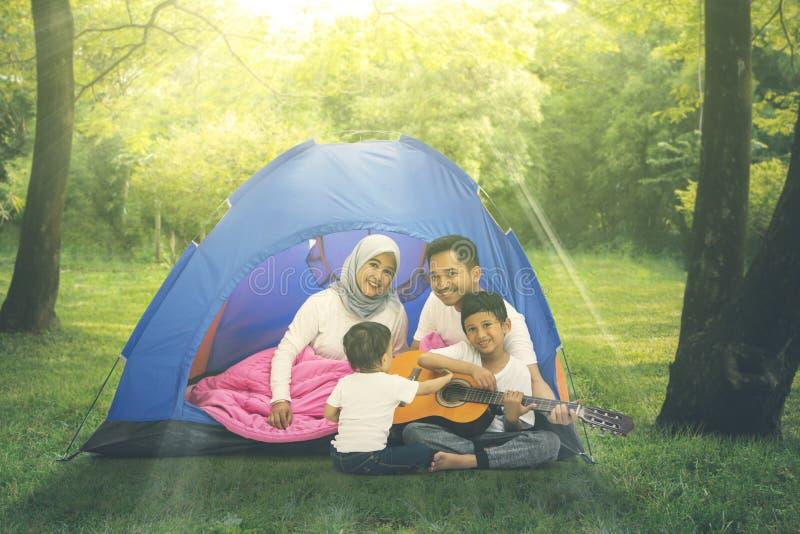 Deux enfants ont plaisir à camper avec leurs parents photos stock