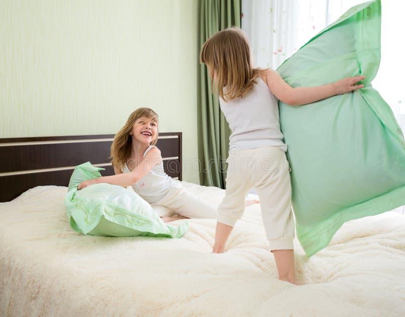 Deux enfants ou enfants jouant ou ont la bataille avec des oreillers dans la chambre à coucher photos libres de droits