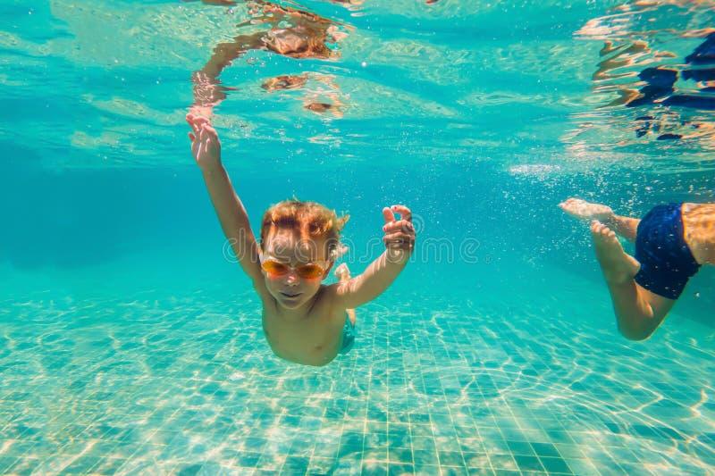 Deux enfants plongeant dans les masques sous l'eau dans la piscine photo libre de droits