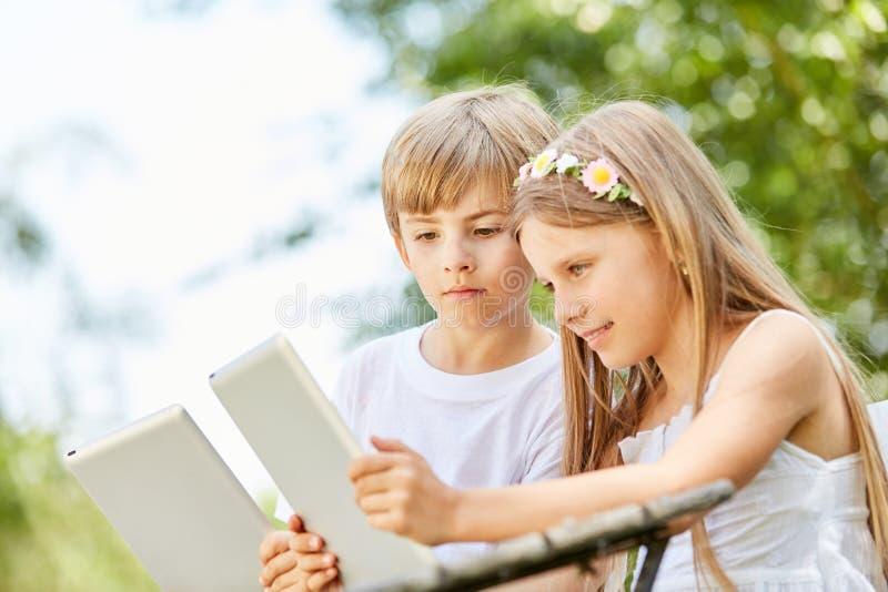 Deux enfants regardent curieusement le comprimé photographie stock libre de droits