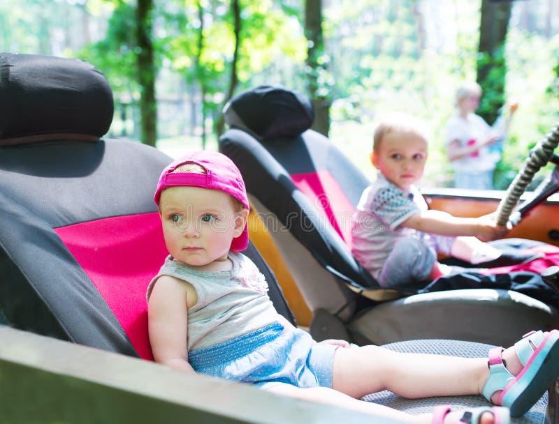 Deux enfants s'asseyent dans la voiture Un enfant conduit l'automobile photo stock
