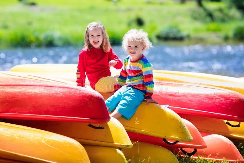 Deux enfants sur des piles de kayak photos stock