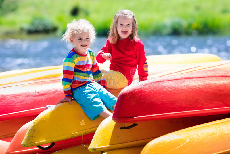 Deux enfants sur des piles de kayak photo stock