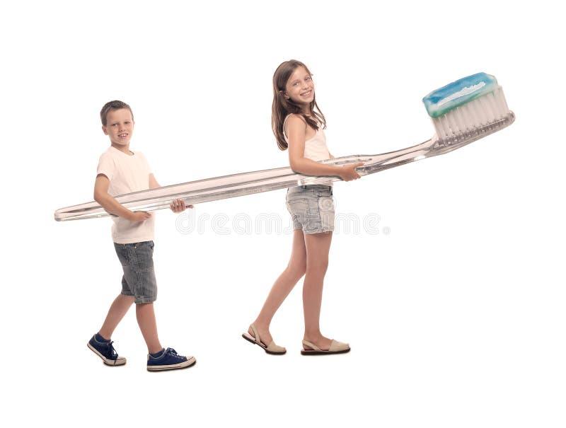 Deux enfants tenant une grande brosse à dents photographie stock