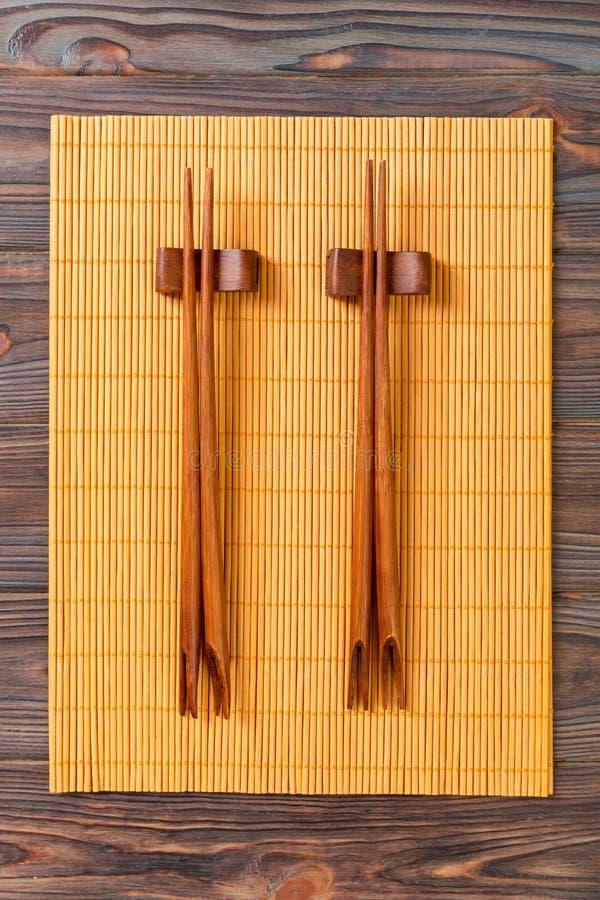 Deux ensembles de baguettes de sushi sur le fond en bambou en bois, vue supérieure photos stock
