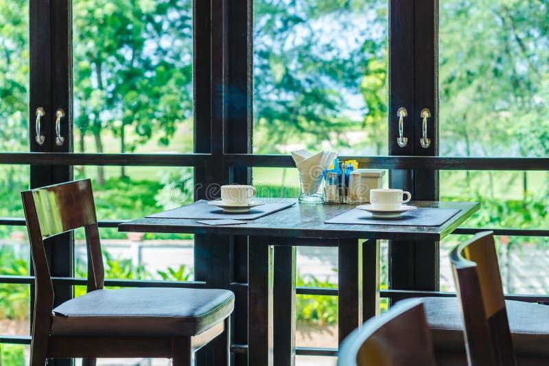 Deux ensembles de table de salle à manger de sièges avec deux tasses de café et condiments sur le dessus photographie stock libre de droits