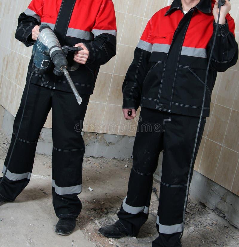 Deux entrepreneurs en bâtiments de sourire dans l'uniforme tenant des outils de construction images stock