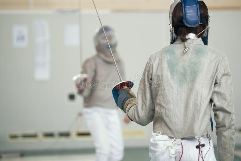 Deux escrimeurs d'adolescent dans des vêtements protecteurs blancs combattant sur le tournoi de clôture photos libres de droits