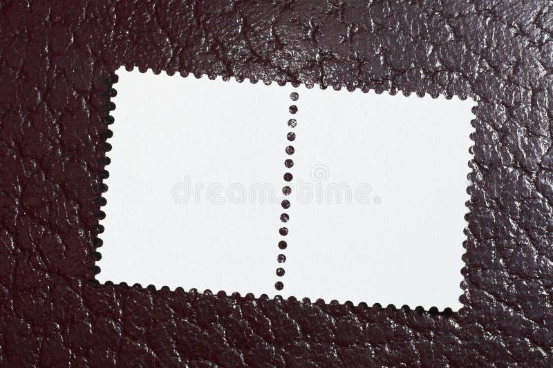 Deux estampilles en blanc sur un fond en cuir rouge images stock