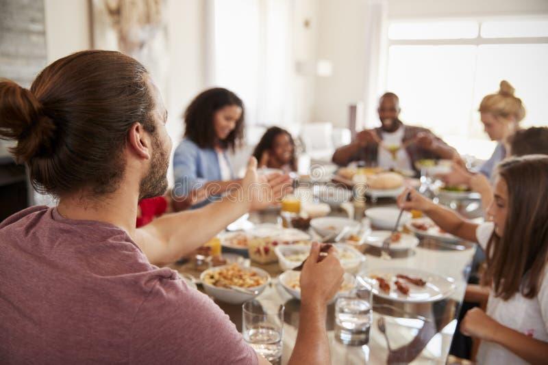 Deux familles appréciant le repas à la maison ensemble photos stock