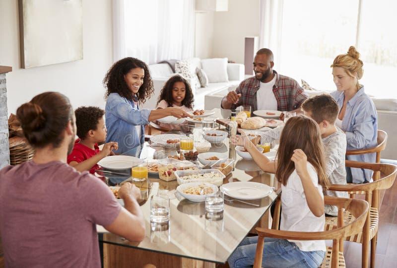 Deux familles appréciant le repas à la maison ensemble image libre de droits