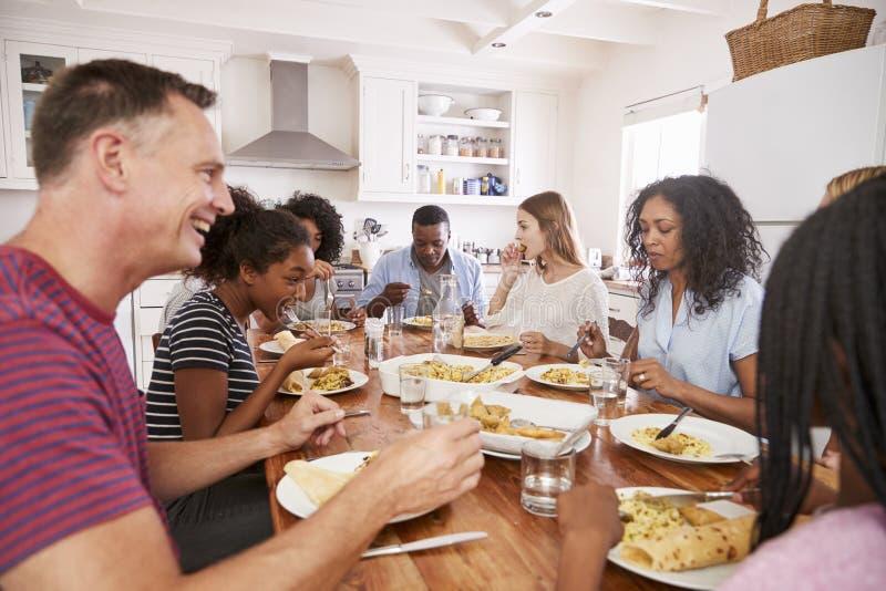 Deux familles appréciant mangeant le repas à la maison ensemble photos libres de droits