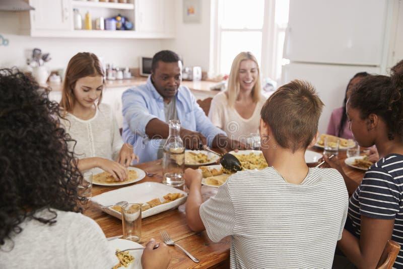 Deux familles appréciant mangeant le repas à la maison ensemble images libres de droits