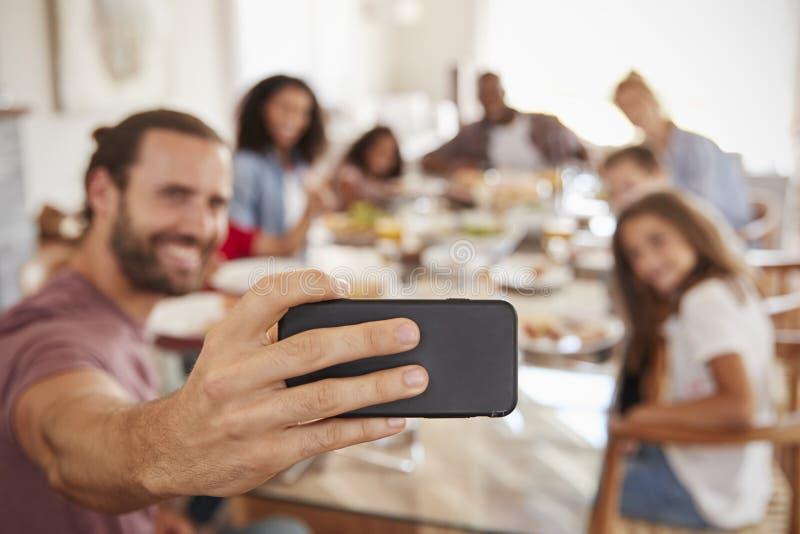 Deux familles prenant Selfie comme elles apprécient le repas à la maison ensemble photos stock