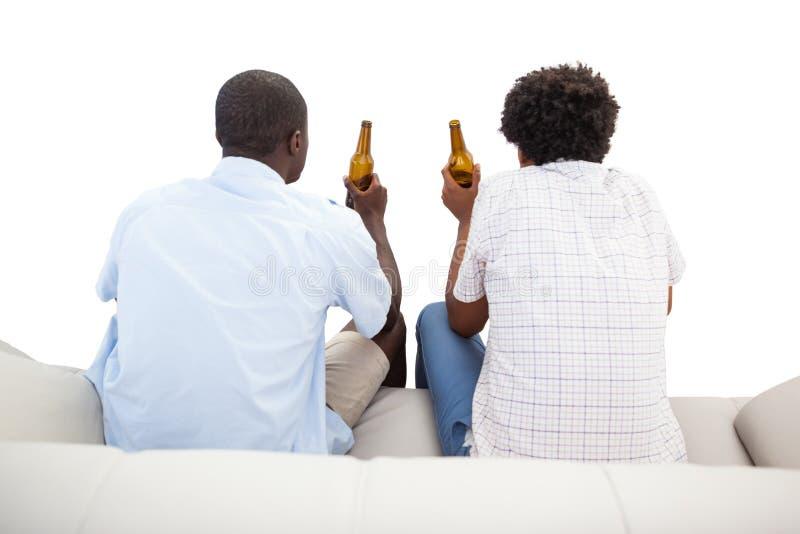 Deux fans de sports se reposant sur le divan avec des bières image libre de droits