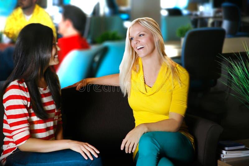 Deux femelles souriant dans l'arrangement créatif parlant et se réunissant photos stock