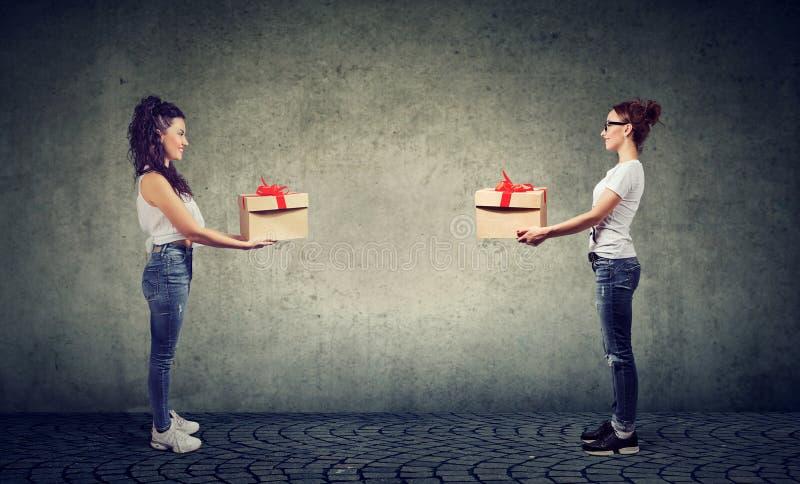 Deux femmes échangeant avec des boîte-cadeau regardant heureusement l'un l'autre images libres de droits