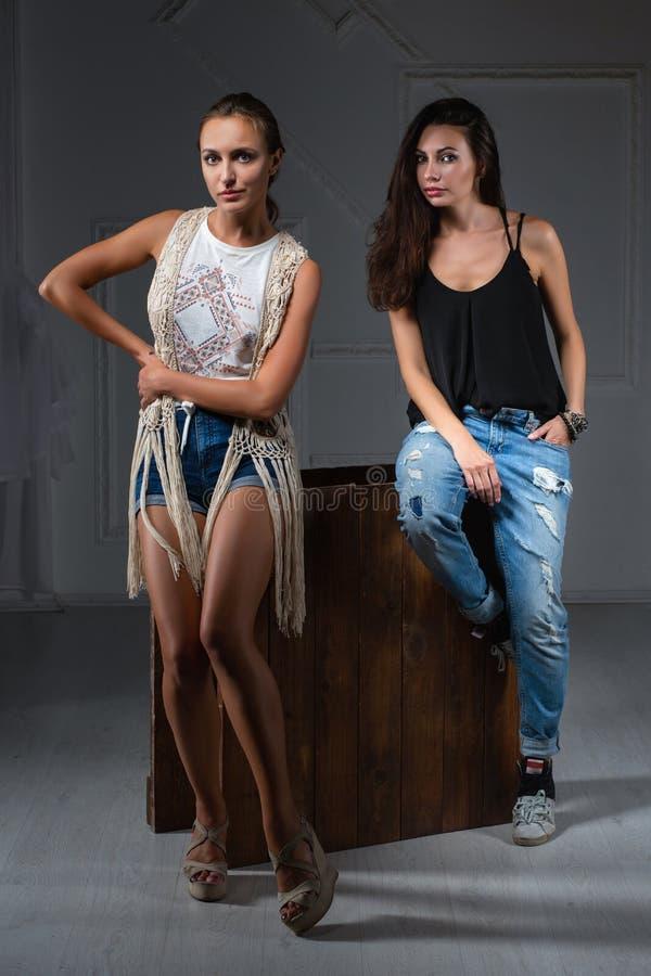 Deux femmes adorables posant dans un studio photo stock