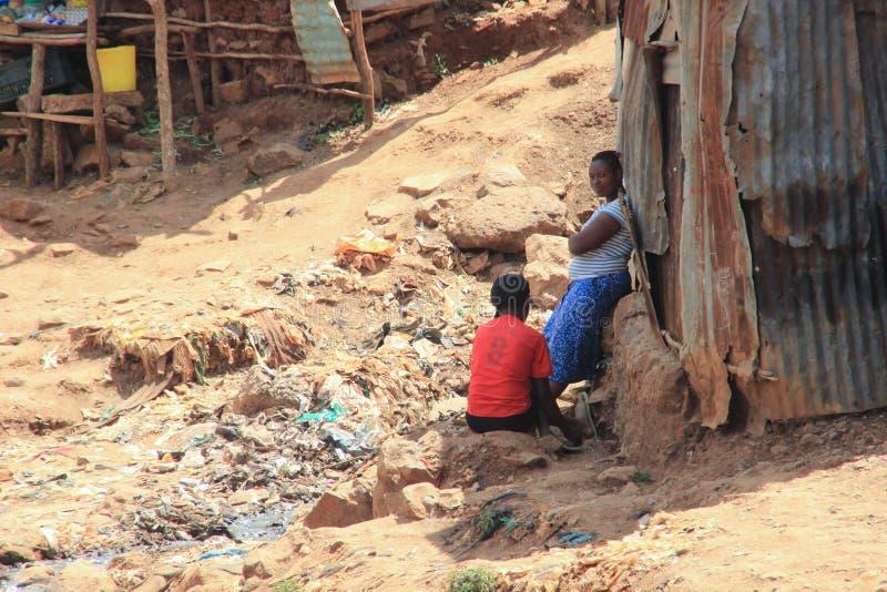deux femmes africaines près des huttes parlent parmi les déchets photo stock