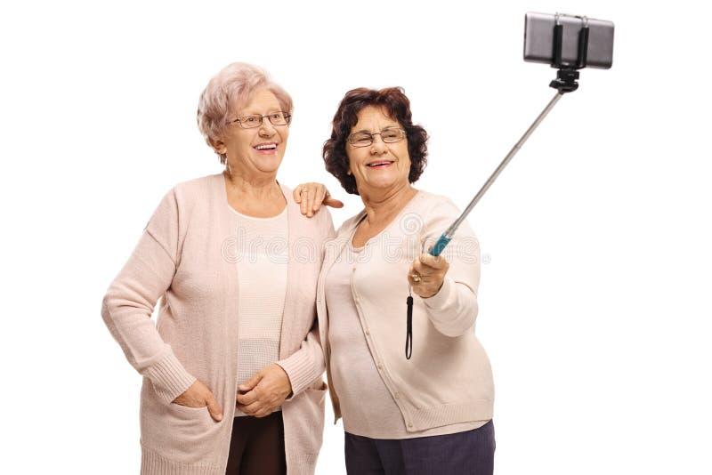 Deux femmes agées prenant un selfie avec un bâton photos stock