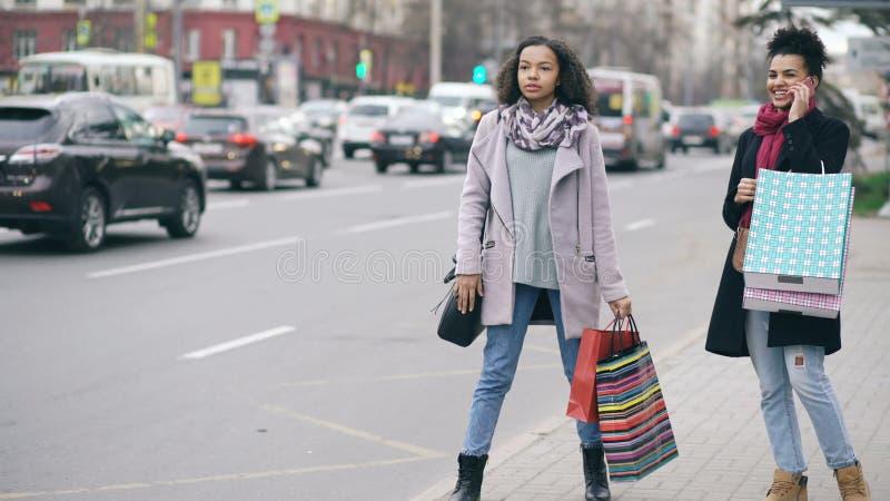 Deux femmes attirantes d'afro-américain avec des paniers réclamant le taxi tout en revenant des ventes de mail banque de vidéos