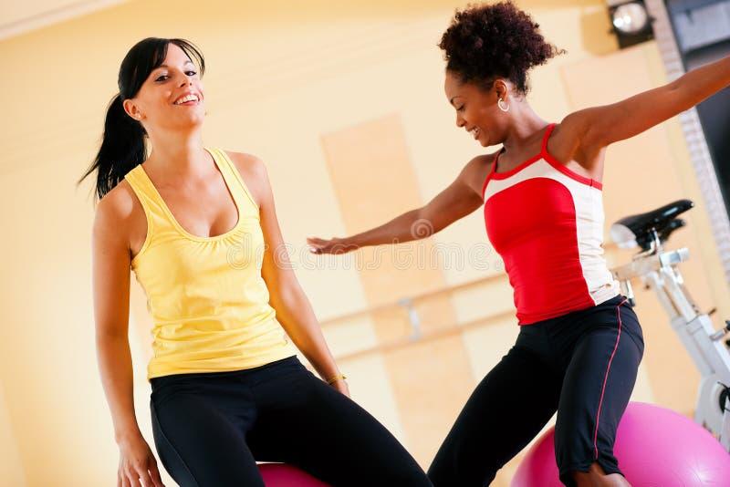 Deux femmes avec la bille de forme physique en gymnastique photos libres de droits