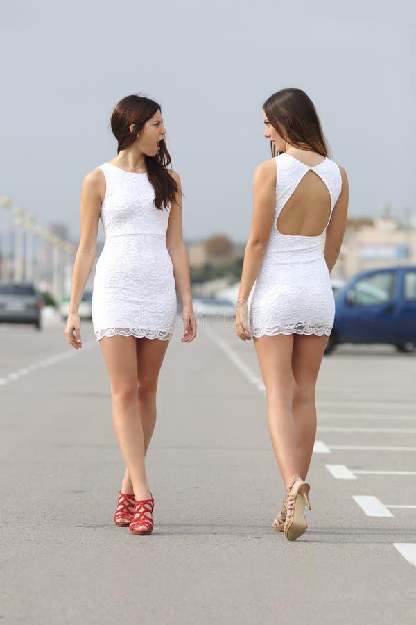 Deux femmes avec la même chose habillent se regarder avec haine photo libre de droits
