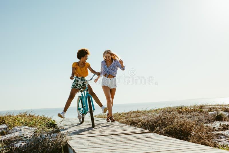 Deux femmes ayant l'amusement avec une bicyclette à la plage images libres de droits