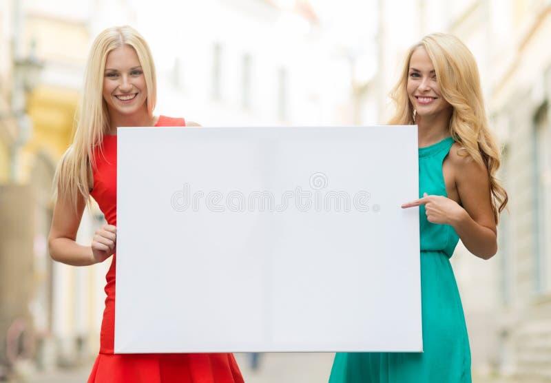 Deux femmes blondes heureuses avec le conseil blanc vide photos libres de droits