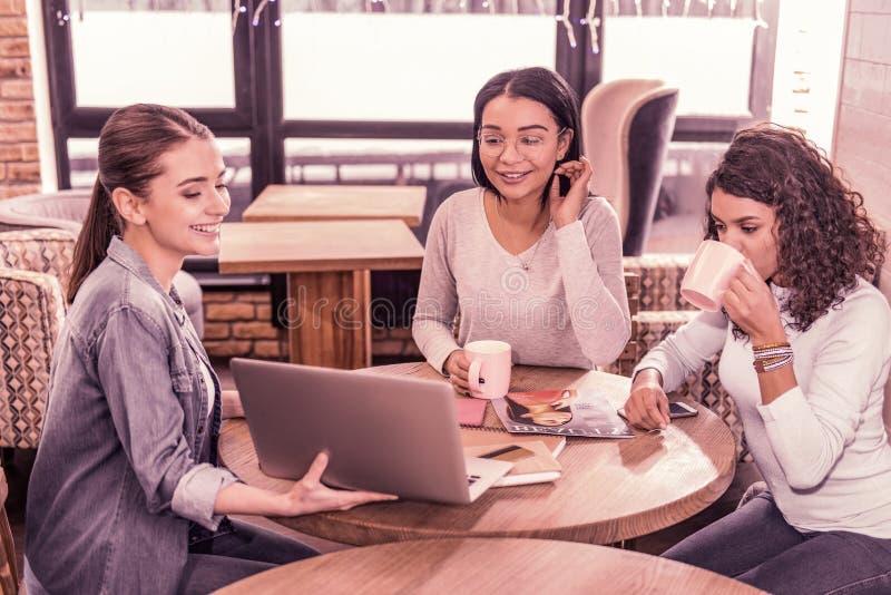 Deux femmes buvant du thé tout en observant la présentation de leur collègue sur l'ordinateur portable photographie stock libre de droits