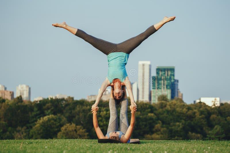 Deux femmes caucasiennes faisant le yoga étirant la séance d'entraînement en parc dehors au coucher du soleil photo stock