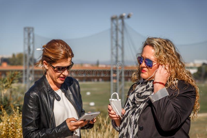 Deux femmes châtains avec leurs périphériques mobiles au milieu d'un grand parc un jour ensoleillé image libre de droits