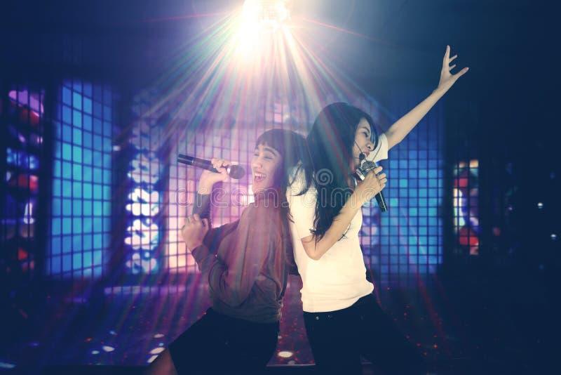 Deux femmes chantant dans la boîte de nuit images stock