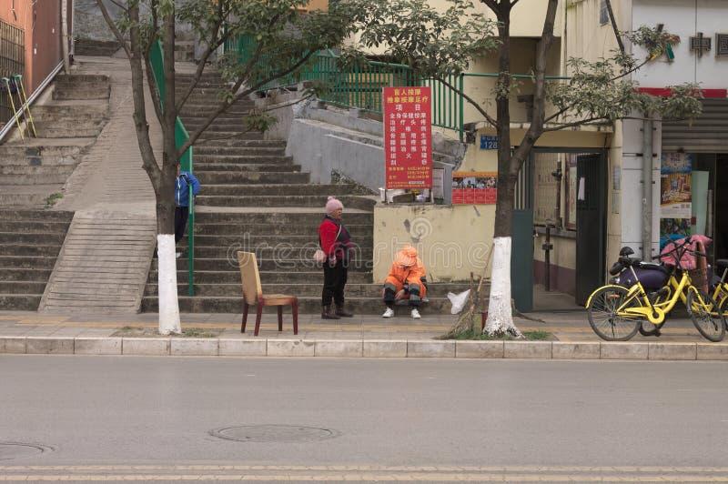 Deux femmes chinoises sur le trottoir avec une chaise images libres de droits