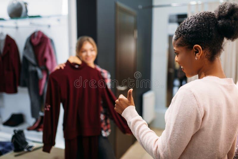 Deux femmes choisissant des vêtements, faisant des emplettes images stock