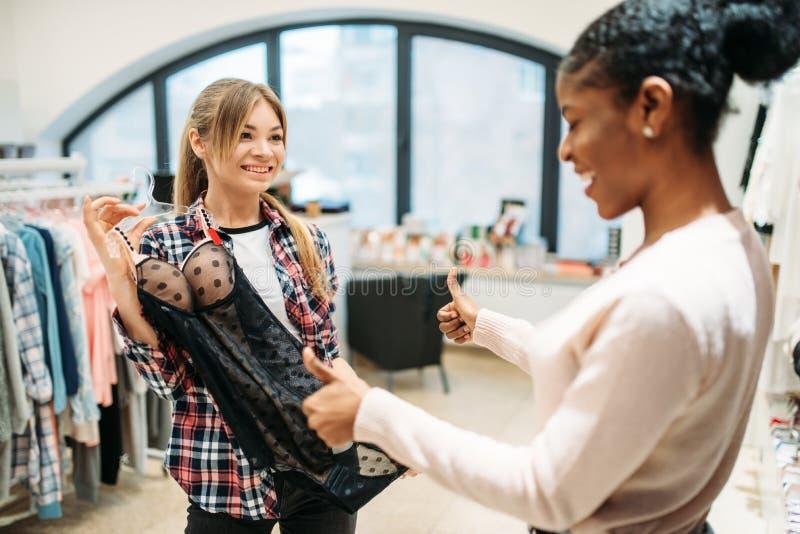 Deux femmes choisissant l'habillement intime, achats images stock